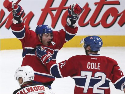 Montreal Canadiens' Andrei Markov (L) celebrates his game-winning goal with teammate Erik Cole (72) during overtime NHL hockey action agains