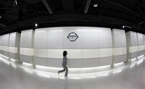 A Nissan Motor showroom employee walks past the company logo at its headquarters in Tokyo January 15, 2009. REUTERS/Kim Kyung-Hoon
