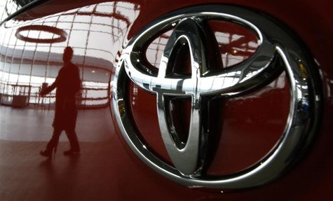 A visitor is reflected on a Toyota vehicle at the company's showroom in Tokyo June 17, 2011. REUTERS/Toru Hanai