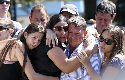 Relatives of Carlos Alexandre Machado, one of the victims of a fire at Boate Kiss nightclub, mourn during his funeral in the southern city o