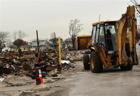 A vehicle makes its way near homes devastated by fire and the effects of Hurricane Sandy in the Breezy Point section of the Queens borough i