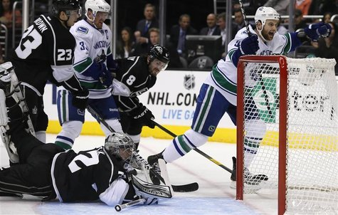Vancouver Canucks' Zack Kassian (R) scores past Los Angeles Kings goaltender Jonathan Quick (bottom) during the first period of their NHL ga