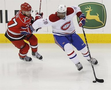 The Montreal Canadiens' P.K. Subban (R) battles the Carolina Hurricanes' Tim Brent for the puck during their NHL hockey game in Raleigh, Nor