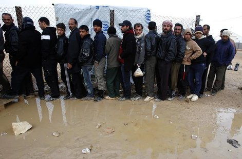 Syrian refugees wait to receive humanitarian aid during a visit by Anne C. Richard, assistant secretary of state for population, refugees, a