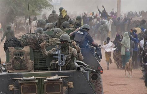 French troops aboard armoured vehicles are greeted by the population as they arrive in Timbuktu in this January 28, 2013 picture provided by