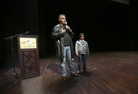 Palestinian journalist Emad Burnat (L) stands next to his son Jibril as he speaks to the audience after a screening of his Oscar-nominated d