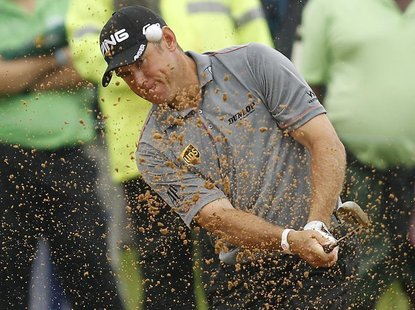 Lee Westwood of England plays a shot out of the bunker on the 14th hole during the final of the 2012 Nedbank Golf Challenge in Sun City, in