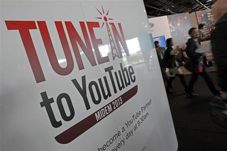 Visitors walk past a YouTube stand during the International Record Music Publishing and Video Music Market (MIDEM) in Cannes January 27, 201