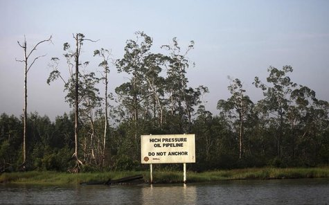 A warning sign belonging to the company Royal Dutch Shell is seen along the Nembe creek in Nigeria's oil state of Bayelsa December 2, 2012.