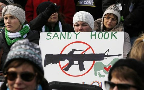 People hold signs memorializing Sandy Hook Elementary School, where 26 children and adults were killed in a mass shooting in December, as th