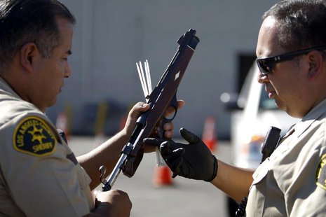 Los Angeles County Sheriff deputies take in guns from motorists trading them in at the 'Gifts for Guns' gun buyback in Compton, California,
