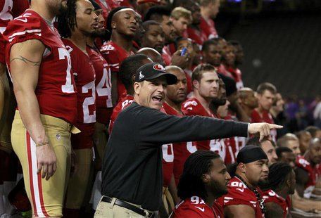 San Francisco 49ers head coach Jim Harbaugh directs his players into position for their team picture during Media Day for the NFL's Super Bo