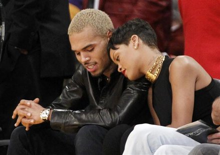 Recording artist Rihanna leans her head on Chris Brown as they sit together courtside at the NBA basketball game between the New York Knicks