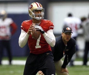 San Francisco 49ers quarterback Colin Kaepernick (L) throws a pass as head coach Jim Harbaugh (R) looks on during practice for the Super Bow