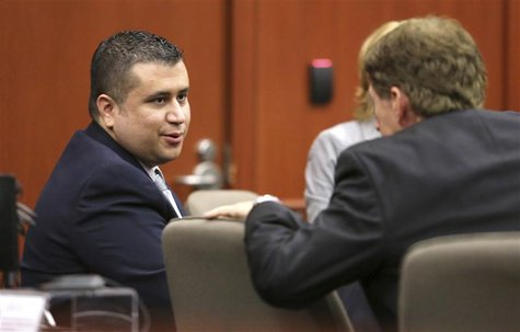 George Zimmerman talks with defense counsel Mark O'Mara at the Seminole County courthouse after a hearing in Sanford, Florida, December 11,