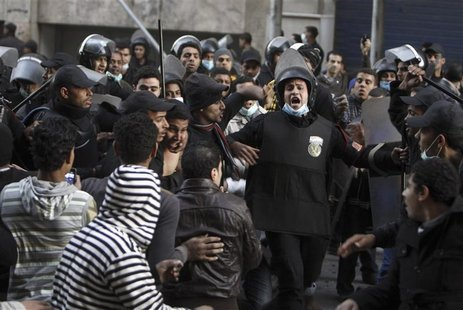 Riot police move in to detain anti-Mursi protesters during clashes in Simon Bolivar Square, which leads to Tahrir Square, in Cairo, January