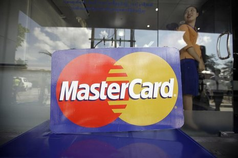 An employee stands behind a MasterCard logo during the launch of the international credit card issuer's first ATM transaction in Myanmar, in