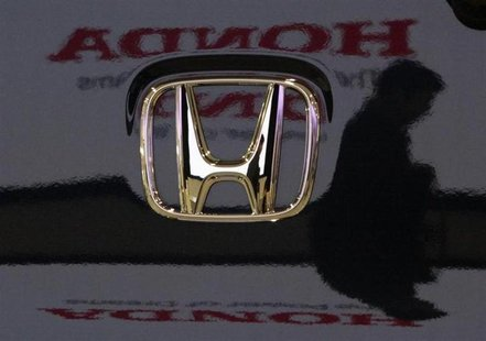 A visitor and the logo of Honda Motor Co are reflected on a Honda car at the company's headquarters in Tokyo January 30, 2009. REUTERS/Toru
