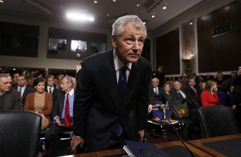 Former Sen. Chuck Hagel (R-NE) (L), sits down before giving testimony to the Senate Armed Services Committee to be Defense Secretary, on Cap