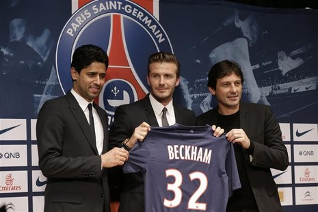 Soccer player David Beckham (C) poses with his new jersey at a news conference in Paris January 31, 2013. Former England captain Beckham has