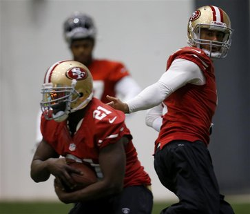 San Francisco 49ers quarterback Colin Kaepernick (R) hands off to running back Frank Gore (L) during practice for the Super Bowl in New Orle