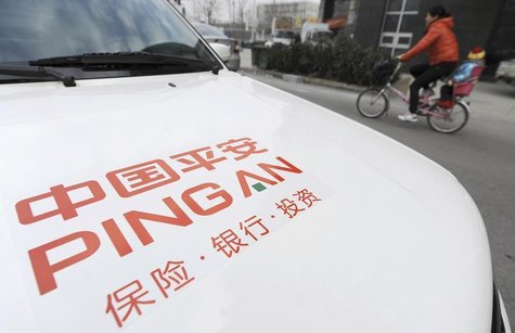 A woman rides a bicycle carrying her child past a car bearing the company logo of Ping An Insurance, in Hefei, Anhui province January 11, 20
