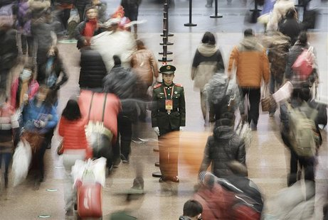 A paramilitary policeman (C) stands guard as passengers walk to board their trains at the Beijing West Railway Station January 31, 2013. REU