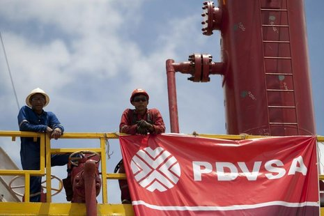 Workers stand in front of a drilling rig at an oil well operated by Venezuela's state oil company PDVSA in Morichal July 28, 2011. REUTERS/C
