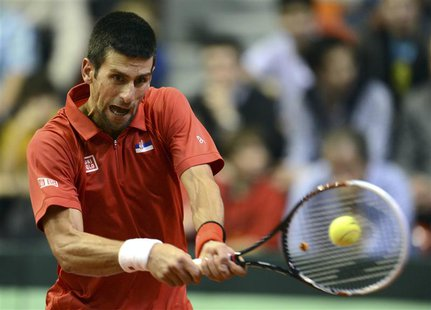Novak Djokovic of Serbia returns the ball to Olivier Rochus of Belgium during their world group first round match in the Davis Cup tennis to