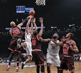 Brooklyn Nets forward Kris Humphries (43) shoots between Chicago Bulls forwards Taj Gibson (22) and Luol Deng (9) as Nets forward Reggie Eva