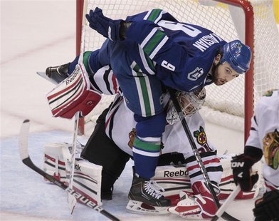 Vancouver Canucks' Zack Kassian steps over Chicago Blackhawks' goaltender Corey Crawford during the second period of their NHL hockey game i