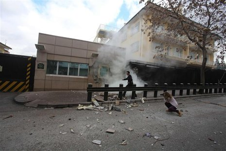 A security officer runs after an explosion at the entrance of the U.S. embassy in Ankara February 1, 2013. A suicide bomber killed a Turkish