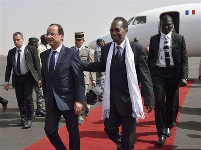 French President Francois Hollande (L) arrives with Mali's interim president Dioncounda Traore at the Bamako airport February 2, 2013. REUTE