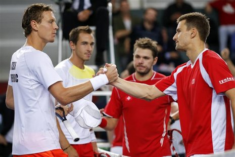 Tomas Berdych (L) of the Czech Republic and his team mate Lukas Rosol (2nd L) shake hands with Stanislas Wawrinka (2R) and Marco Chiudinelli