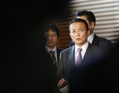 Japan's Finance Minister Taro Aso is seen in-between reporters while he speaks at a joint news conference with Bank of Japan Governor Masaak