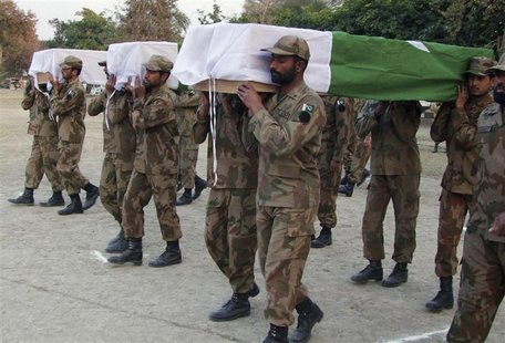 Pakistani soldiers carry the flag-draped caskets of their colleagues killed in an attack by militants during their funeral ceremony in Bannu