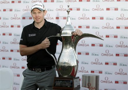 Stephen Gallacher of Scotland poses with the trophy at the 18th green after the fourth and final round of the Dubai Desert Classic at the Em