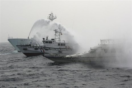 A Japan Coast Guard patrol ship (L) sprays water at a fishing boat (R) carrying Taiwanese activists onboard while it heads for the disputed