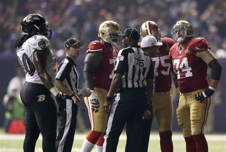 San Francisco 49ers and Baltimore Ravens players gather on the field during a power outage in the NFL Super Bowl XLVII football game in New