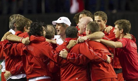 Team Canada's head coach Martin Laurendeau (white cap) celebrates with his team after Canada's Milos Raonic defeated Spain's Guillermo Garci