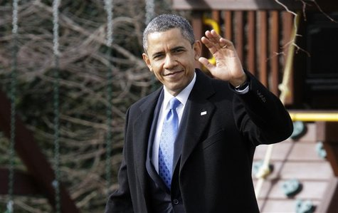 U.S. President Barack Obama waves to reporters as he walks across the South Lawn to board the Marine One helicopter for departure to Minneso