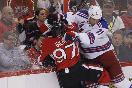 Ottawa Senators' Matt Gilroy (L) is checked into the boards by New York Rangers' Mike Rupp during the first period in Game 3 of the NHL East