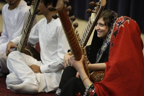 A girl smiles after playing the sitar during a performance by members of the Young Afghan Traditional Ensemble at the State Department in Wa