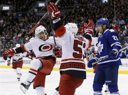 Carolina Hurricanes' Patrick Dwyer (L) celebrates his goal with teammate Jeff Skinner (C) in front of Toronto Maple Leafs' James van Riemsdy