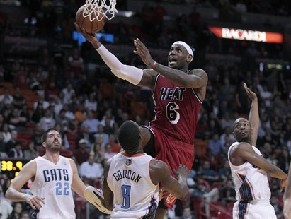 Miami Heat's LeBron James drives against Charlotte Bobcats' Byron Mullens (L), Ben Gordon (C) and Kemba Walker in the second half of their N