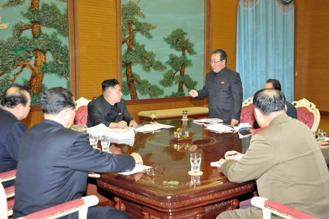 North Korean leader Kim Jong-Un (C) presides over a consultative meeting with officials about state security and foreign affairs in this und