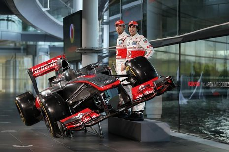 McLaren Formula One drivers Jenson Button of Britain (L) and Sergio Perez of Mexico pose for photographers after unveiling the McLaren MP4-2