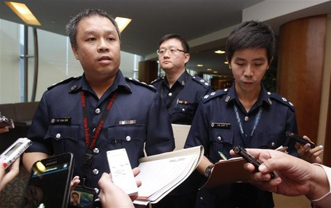 Superintendent Ho Yenn Dar (L), assistant director of media relations of Singapore Police Force listens to questions from journalists on the