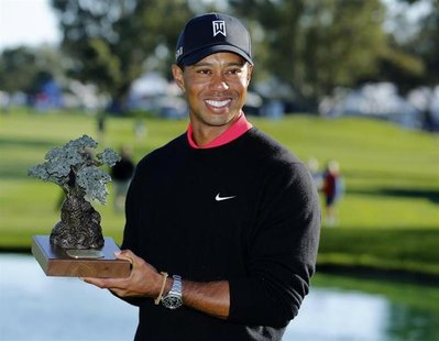 U.S. golfer Tiger Woods holds the trophy after winning the Farmers Insurance Open in San Diego, California January 28, 2013. REUTERS/Mike Bl