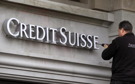 A worker uses a cordless screwdriver to fix the logo of Swiss bank Credit Suisse at a branch office in Zurich February 4, 2013. REUTERS/Arnd